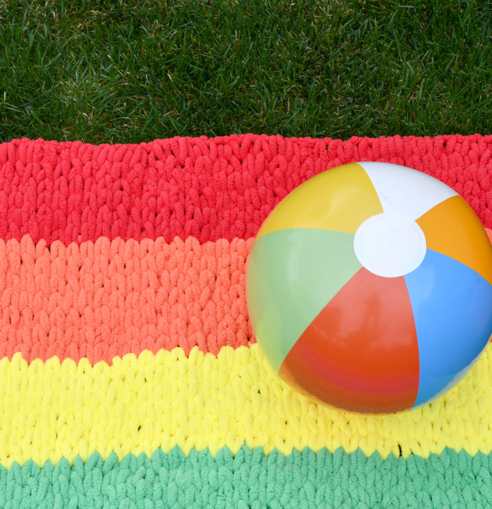 How To Make A Rainbow Blanket with Loop Yarn - image Rainbow-Finger-Knit-Blanket-Free-Pattern-990x1024 on https://knitting-crocheting-yarn.com
